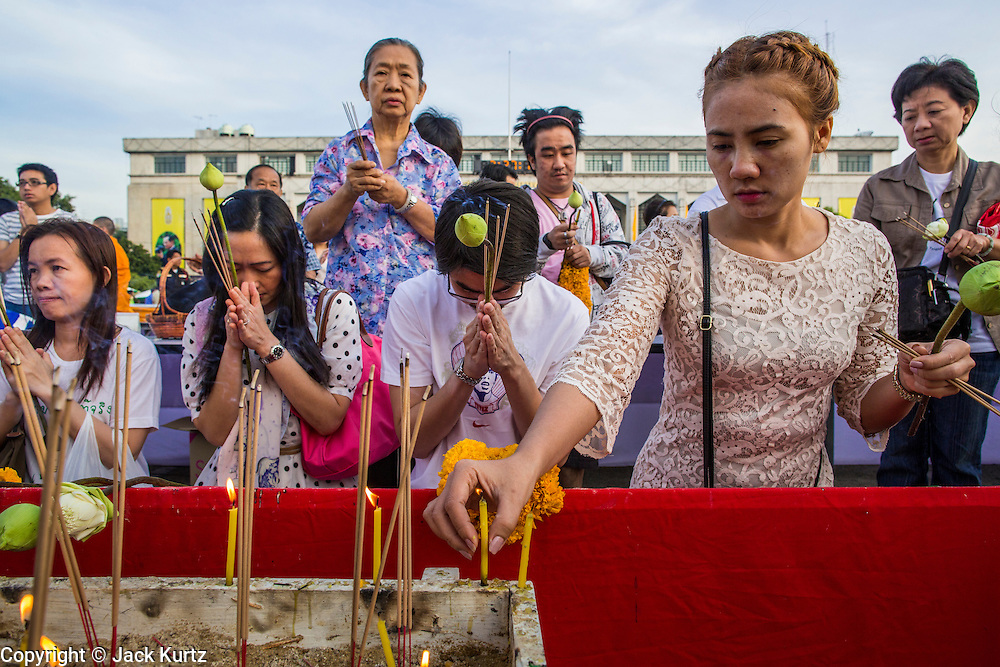 "01 JANUARY 2013 - BANGKOK, THAILAND:  People light candles and pray at a shrine during a special merit making ceremony at Bangkok City Hall New Year's morning. Many Thais go to Buddhist temples and shrines to ""make merit"" for the New Year. The traditional Thai New Year is based on the lunar calender and is celebrated in April, but the Gregorian New Year is celebrated throughout the Kingdom.     PHOTO BY JACK KURTZ"