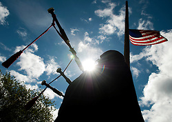 NEWS&GUIDE PHOTO / PRICE CHAMBERS.The American Flag flies at half mast as David Macfarlane gets in position at the Aspen Hill Cemetery. He plays Amazing Grace and other traditional songs on the bagpipes for those attending the graveside ceremony.