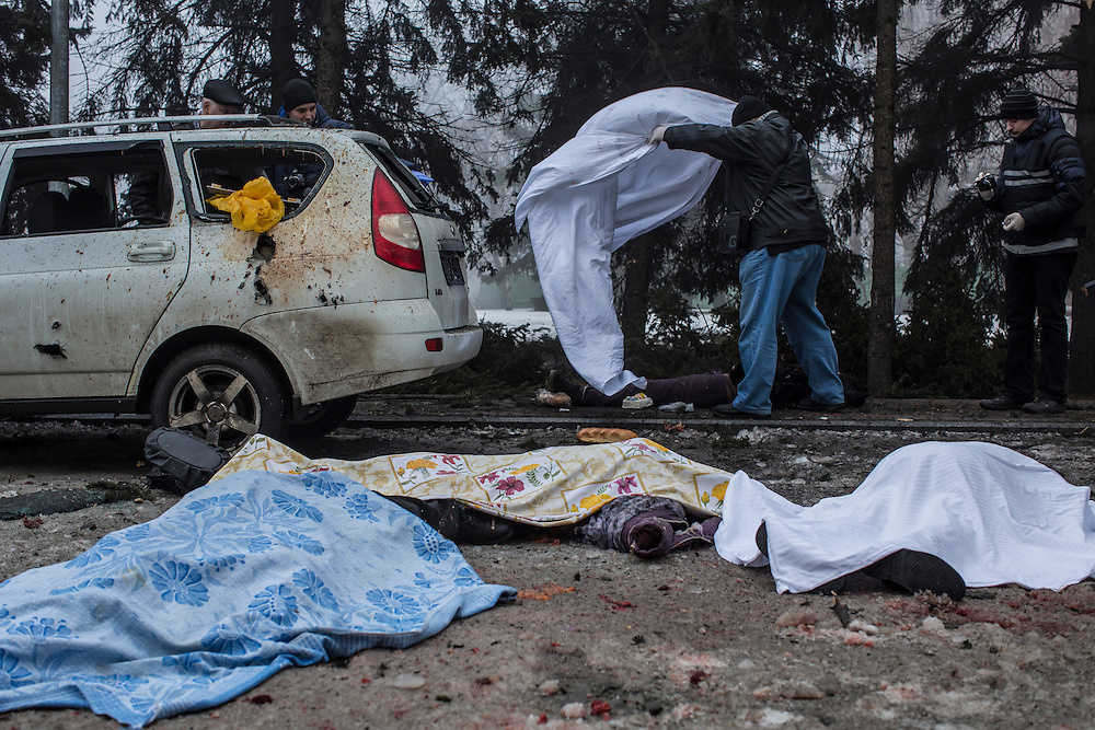 DONETSK, UKRAINE - JANUARY 30, 2015: Investigators cover the body of one of four people who were killed when a rocket struck the parking lot outside a center where humanitarian aid was being distributed in Donetsk, Ukraine. A fifth person was killed in a parked car, and at least two others died in a separate shelling nearby. CREDIT: Brendan Hoffman for The New York Times