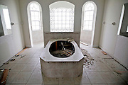 A bathroom, stripped of everything, including the tub, sits in shambles at a house in Cape Coral, Fla. Greg Kahn/Staff