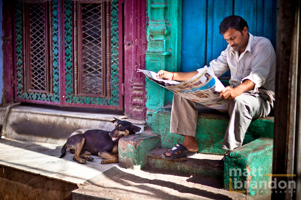 A man reads a newspaper  on the steps in the streets of old Delhi.