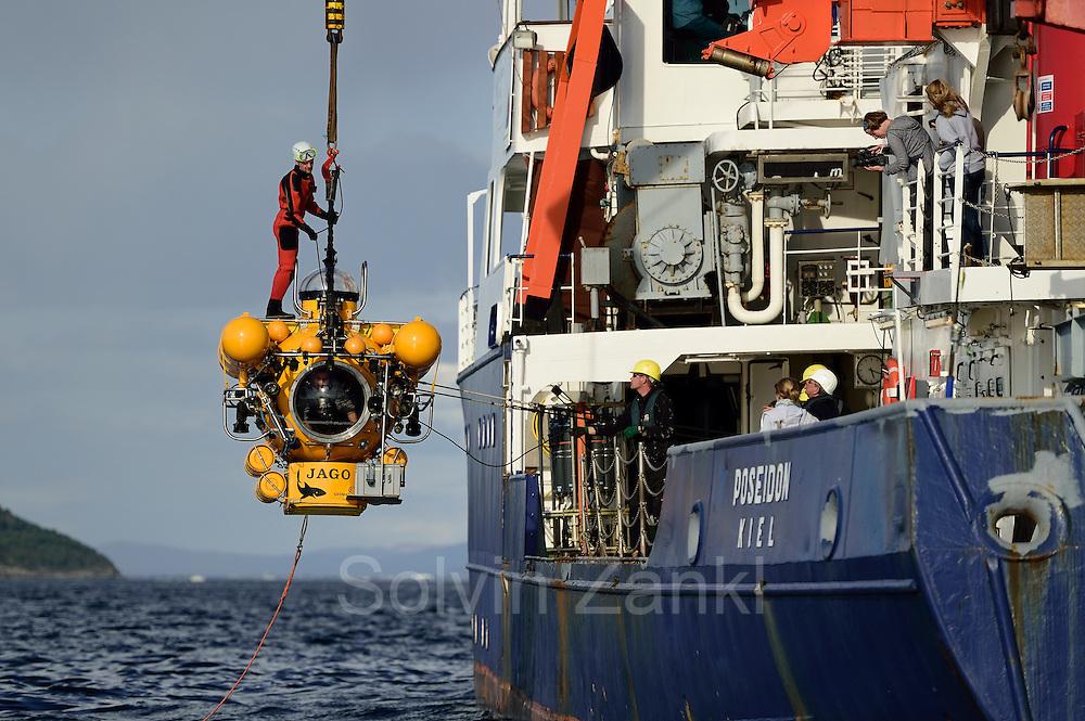 """Das Forschungstauchboot JAGO wird im Trondheimfjord von der FS Poseidon aus zu Wasser gelassen. Zum Lösen des Hakens ist ein Helfer im Taucheranzug mit """"an Bord"""". Trondheimfjord Norwegen"""