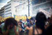 People run from continuous amounts of tear gas thrown at them.  On the day of the 29/6/2011 the police had used over an excess of 150,000 euro worth of tear gas and stun grenades in Athens, Greece. Image © Angelos Giotopoulos/Falcon Photo Agency