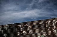 A US Border Patrol helicopter patrols the border separating Tijuana, Mexico and San Diego, California, USA from above.  Colonia Libertad, Tijuana, Baja California, Mexico.