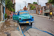 Old car in Santiago de Cuba being sanded for painting, Cuba.
