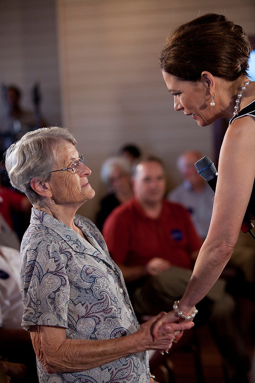 Republican presidential hopeful Michele Bachmann, right, holds the hands of an audience member during a campaign stop on Sunday, July 24, 2011 in Muscatine, IA.