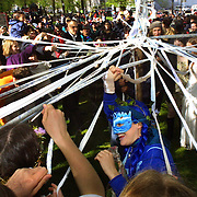 Many costumed participants dance around a May pole in the North Park Blocks as May Day march festivities get under way.