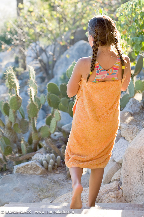 Young girl in swimsuit & towel in desert locale.