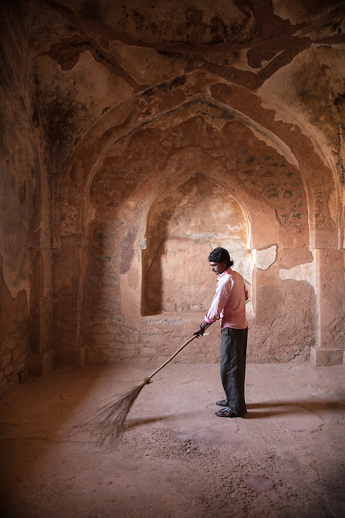 in Mandu India man sweeping ruins