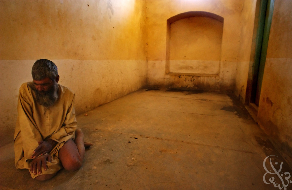 A mentally ill Afghan man sits alone in a barren room at the Afghanistan Red Crescent Society May 16, 2002 in Kandahar.