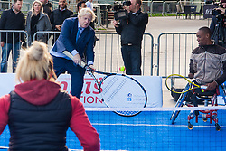 City Hall, London, November 24th 2014. Mayor Boris Johnsonwelcomes the world's best wheelchair tennis players with a game of mini tennis outside City Hall. The players are in London to compete in the NEC Wheelchair Tennis Masters 2014, being held at the Lee Valley Hockey and Tennis Centre, being held from 26 - 30 November. PICTURED: Using a giant tennis raquet, Mayor Boris Johnson has a knock-about with wheelchair tennis players Lucas Sithole (South Africa) and Jordanne Whiley (Great Britain).
