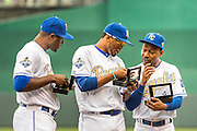 KANSAS CITY, MO - APRIL 5, 2016: Lorenzo Cain #6, Alcides Escobar #2 and Jarrod Dyson #1 of the Kansas City Royals examine their 2015 World Series Championship rings after receiving them during pre-game ceremonies before the game between the New York Mets and the Kansas City Royals at Kauffman Stadium on April 5, 2016 in Kansas City, Missouri. (Photo by Jean Fruth)