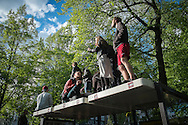 """01/05/2015 – Berlin, Germany: A group of people hangout on top of a bus stop in Kreuzberg during the """"Myfest"""" street festival. """"Myfest"""" takes place in district SO 36, the traditional centre of riots that usually occur during May Day celebrations and it was organized to decreased the violence caused by Revolutionary May Day Demonstrations.  The radical left wing criticises such events claiming that it is pretended to pacify social conflicts and to ban radical demonstrations. The International Workers Day is a celebration of laborers and the working classes that is promoted by the international labor movement, anarchists, socialists, and communists and occurs every year on May Day. (Eduardo Leal)"""