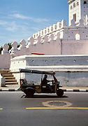 Tuk-tuk drives past part of Bangkok's old fortress walls