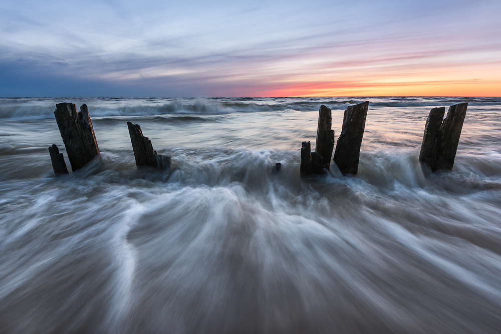 Lake Michigan's waves rush past old pilings at sunset. <br />