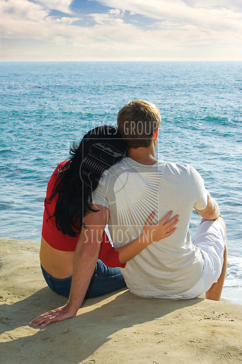 young couple sitting on the bluffs overlooking the Pacific Ocean