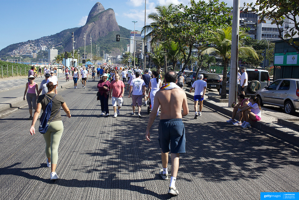 Walkers exercise early on Sunday morning at Ipanema Beach. On Sunday's the main roads along the beaches of Copacabana, Leblon and Ipanema are closed to traffic bringing out thousands of people of all ages to walk, run, jog, ride, skateboard and cycle more than 10 km of beachside roadway. Rio de Janeiro,  Brazil. 4th July 2010. Photo Tim Clayton..The beaches of Rio de Janeiro, provide the ultimate playground for locals and tourists alike. Beach activity is in abundance as beach volley ball, football and a hybrid of the two, foot volley, are played day and night along the length and breadth of Rio's beaches. .Volleyball nets and football posts stretch along the cities coastline and are a hive of activity particularly at it's most famous beaches Copacabana and Ipanema. .The warm waters of the Atlantic Ocean provide the ideal conditions for a variety of water sports. Walkways along the edge of the beaches along with exercise stations and cycleways encourage sporting activity, even an outdoor gym is available at the Parque Do Arpoador overlooking the ocean. .On Sunday's the main roads along the beaches of Copacabana, Leblon and Ipanema are closed to traffic bringing out thousands of people of all ages to walk, run, jog, ride, skateboard and cycle more than 10 km of beachside roadway. .This sports mad city is about to become a worldwide sporting focus as they play host to the world's biggest sporting events with Brazil hosting the next Fifa World Cup in 2014 and Rio de Janeiro hosting the Olympic Games in 2016...