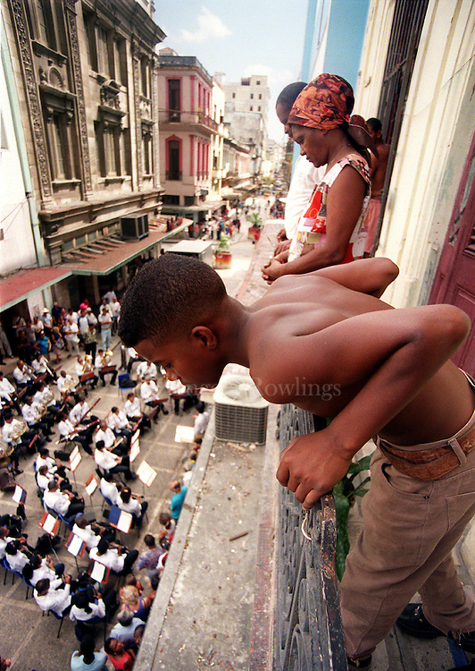 A teen watches an orchestra play from his balcony in Havana.