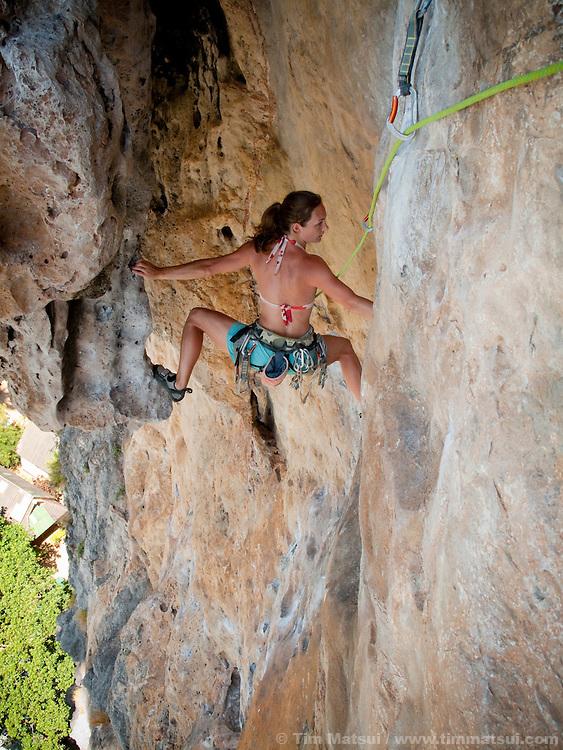 A caucasian woman climbs limestone cliffs in Tonsai, Thailand.