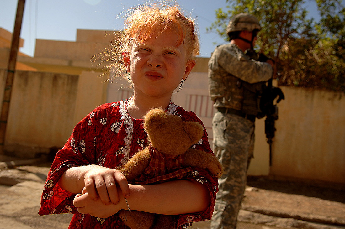 An Iraqi girl carrying a teddy bear walks the street with soldiers from Bravo Company 1/17th Infantry 172nd Stryker BDE Ft. Wainwright, Alaska, on June 16, 2006 during a foot patrol in Badush west of Mosul, Iraq. — © TSgt Jeremy Lock/