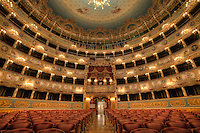 """Teatro La Fenice (""""The Phoenix"""") in Venice, is one of the most famous and renowned landmarks in the history of Italian theatre as well as those in Europe. La Fenice has faced serious fires twice in its life (1836 and 1996) but risen again as its name (Phoenix) would demand of it. Now restored to its 18th-century glory, the famous opera house boasts a jaw-dropping interior that displays a late-Empire luxury of gilt decorations, plushy extravagance and stucco."""