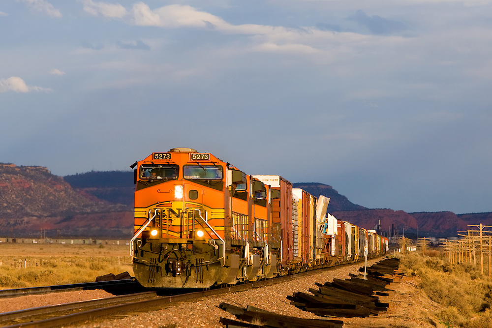 Heading into the late afternoon sun, a BNSF freight train passes the colorful cliffs east of Gallup, NM.