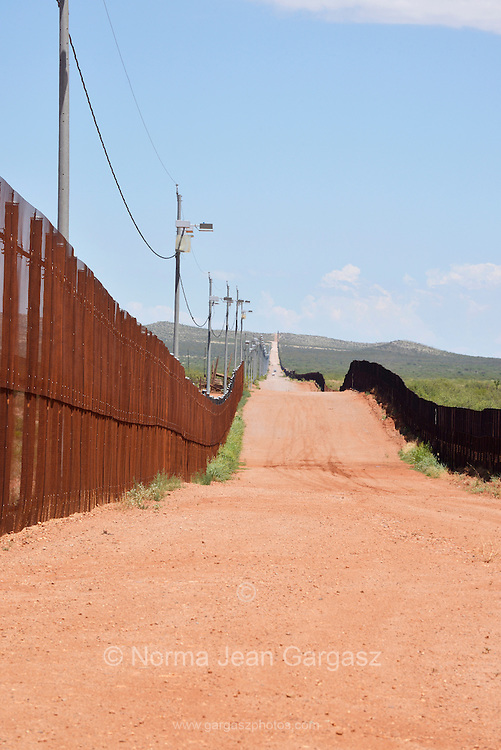 The international border between Naco, Arizona, USA and Naco, Sonora, Mexico is indicated by a metal wall.