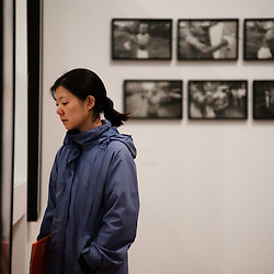London, UK - 8 October 2012: a visitor looks up at pictures by Daido Moriyama at Tate Modern. The exhibition examine the relationship between the work of William Klein (b.1928) and that of Daido Moriyama (b.1938). Taking as its central theme the cities of New York and Tokyo, the show explores both artists' celebrated depictions of modern urban life.