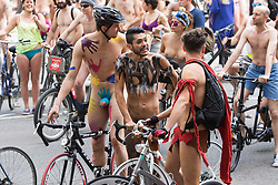 Westminster Bridge, London, June 11th 2016. Hundreds of naked and semi-naked cyclists participate in the World Naked Bike Ride that takes place in cities around the world, to highlight the alternatives to hydrocarbon fuels. PICTURED: Men in body paint wait for friends to catch up with them.