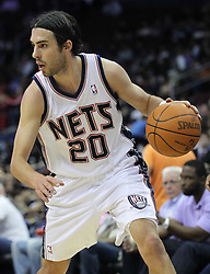 Apr 11; Newark, NJ, USA; New Jersey Nets shooting guard Sasha Vujacic (20) dribbles the ball during the first half at the Prudential Center.