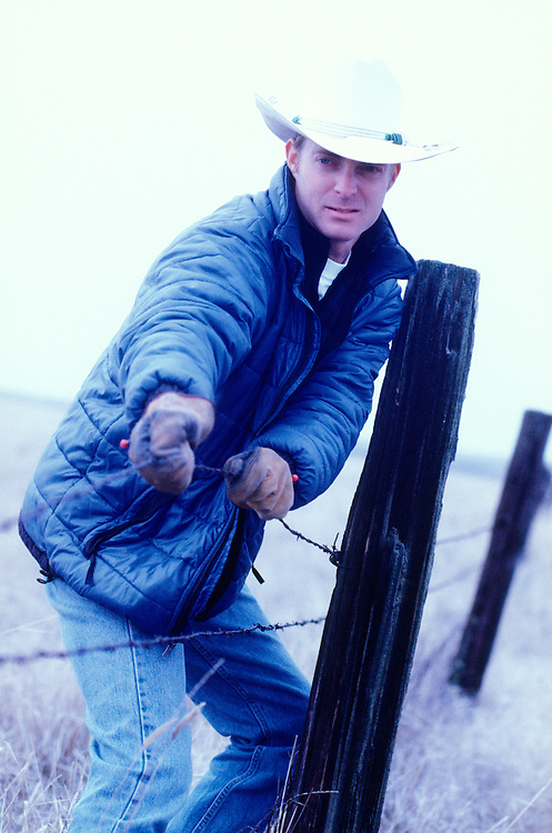 A man wearing a jacket and cowboy hat mending a barbed wire fence.