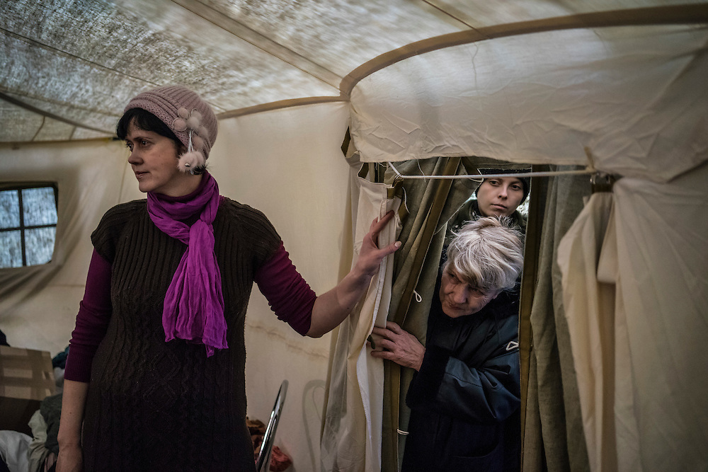 People peer into a tent where free second-hand clothes are available to those displaced by fighting between pro-Russia rebels and Ukrainian forces in Eastern Ukraine, a service offered at a processing center for internally displaced people located at the train station, on Monday, February 9, 2015 in Slovyansk, Ukraine.