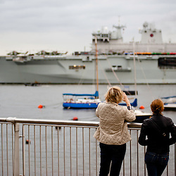 London, UK - 13 July 2012: Londoners watch Royal Navy's biggest ship HMS Ocean sailing up Thames towards Greenwich as part of the security plan for the Olympic Games.