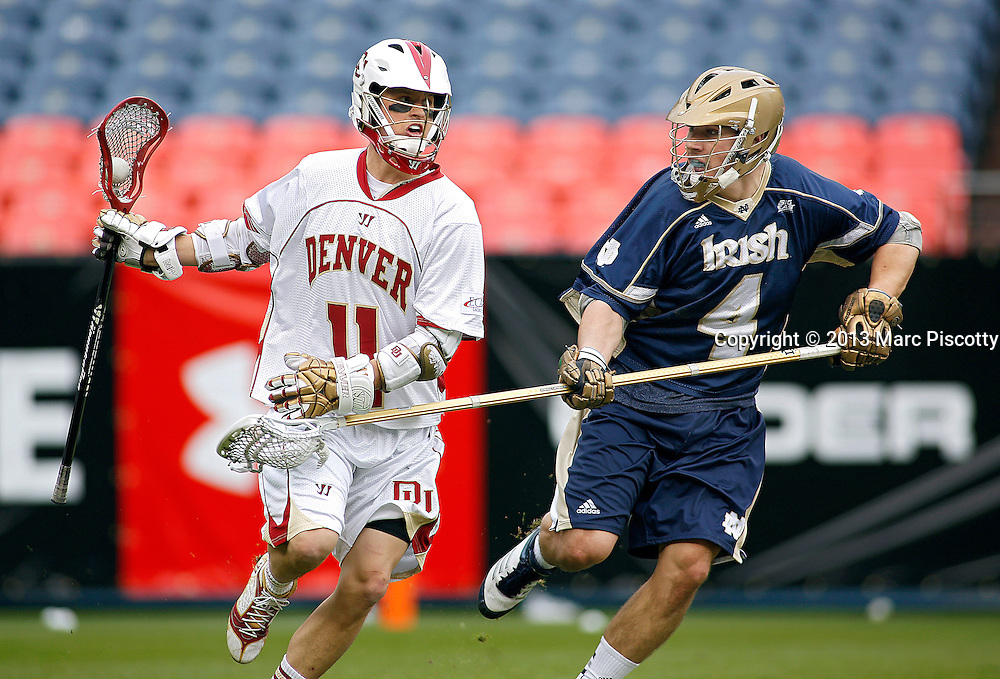 SHOT 3/16/13 3:47:39 PM - Denver's Eric Law #11 shields the ball while attacking from Notre Dame's Stephen O'Hara #4 during their college lacrosse game at the Whitman's Sampler Mile High Classic at Sports Authority Field at Mile High in Denver, Co. on Saturday March 16, 2013. Notre Dame won the game 13-12 in overtime. (Photo by Marc Piscotty / © 2013)