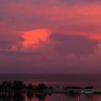Storm clouds over the Atlantic Ocean off Miami, Florida reflect the reddish light of the setting sun on a summer evening.