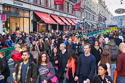th 2014. Tens of thousands of shoppers flood central London as  Black Friday discounts and most people's pay days kick off the Christmas shopping season in earnest. PICTURED: Crowds of shhoppers break through barriers seaparating them from resurfacing works on Regent Street.