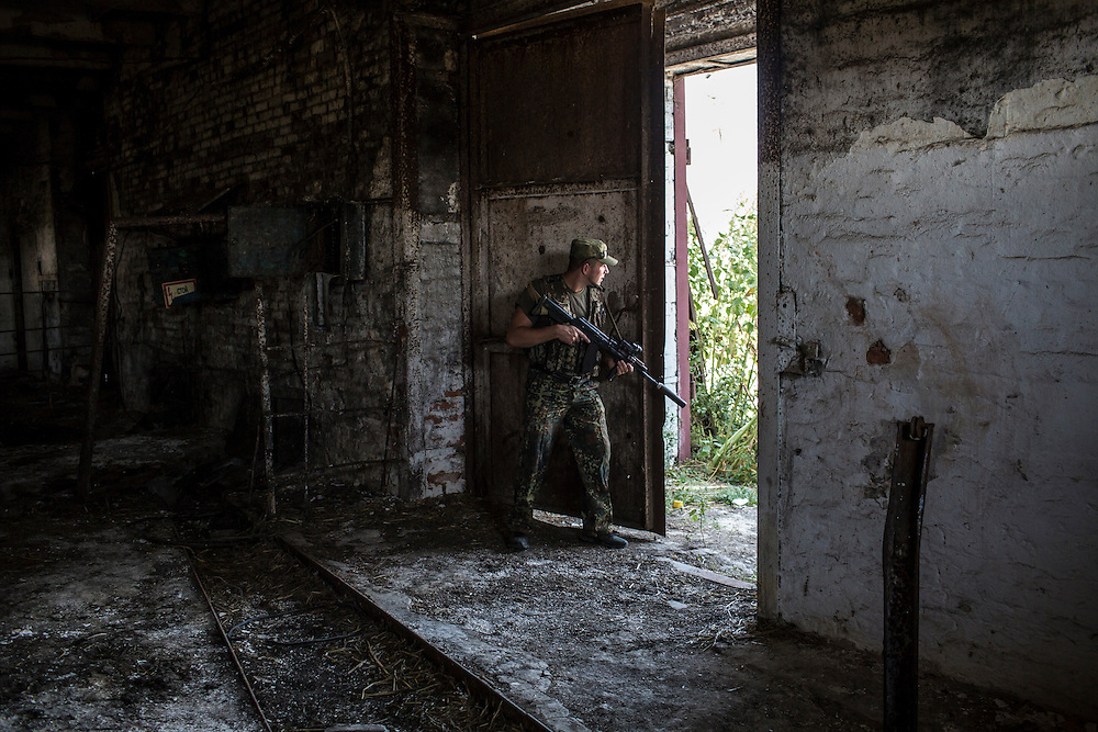 CHERMALYK, UKRAINE - AUGUST 29, 2015: A Ukrainian soldier looks from a farm building toward the nearby Kalmius River and rebel-held territory in Chermalyk, Ukraine. Two days earlier, the farm was shelled by rebels based nearby, with a level of skill that the soldiers felt indicated they were being targeted by professional Russian soldiers rather than rebel irregulars. CREDIT: Brendan Hoffman for The New York Times