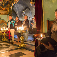 Israel, Jerusalem, Greek Orthodox priest reading by light of candle by line of tourists inside gloomy interior of Church of Holy Sepulchre