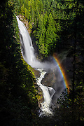 """A bright rainbow forms in the mist of Wallace Falls, a 367-foot (112 meter) waterfall that is the tallest of three falls in Wallace Falls State Park near Gold Bar, Washington. Wallace Falls was named for Joe and Sarah Kwayaylsh, members of the Skykomish tribe, who were the first homesteaders in the area; """"Wallace"""" is a mispronounciation of their name."""