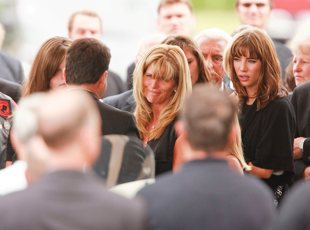 Dani Probert, Bob Probert's widow, speaks with pall bearers following her husband's funeral at the Windsor Christian Fellowship church in Windsor, Ontario July 9, 2010. The Detroit Red Wings enforcer died suddenly at the age of 45 while boating with his family.<br /> The Canadian Press/GEOFF ROBINS