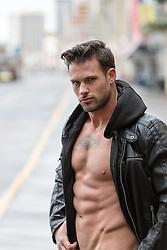 hot man without a shirt in a leather jacket outdoors