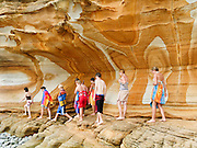 """Young swimmers explore coastal sandstone rock patterns exposed in the Painted Cliffs, in Maria Island National Park, near Darlington, Tasmania, Australia. Undercut by the Tasman Sea (South Pacific Ocean), the Painted Cliffs date from the Permian and Triassic, 300-200 million years ago. Published in """"Light Travel: Photography on the Go"""" book by Tom Dempsey 2009, 2010."""
