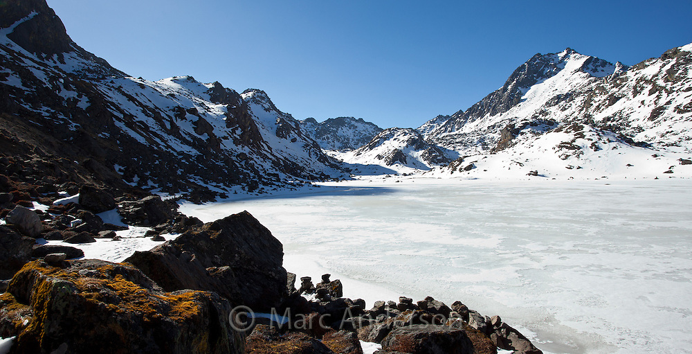 Frozen lake at Gosaikunda, a high altitude stop for trekkers in the Himalayas, Nepal