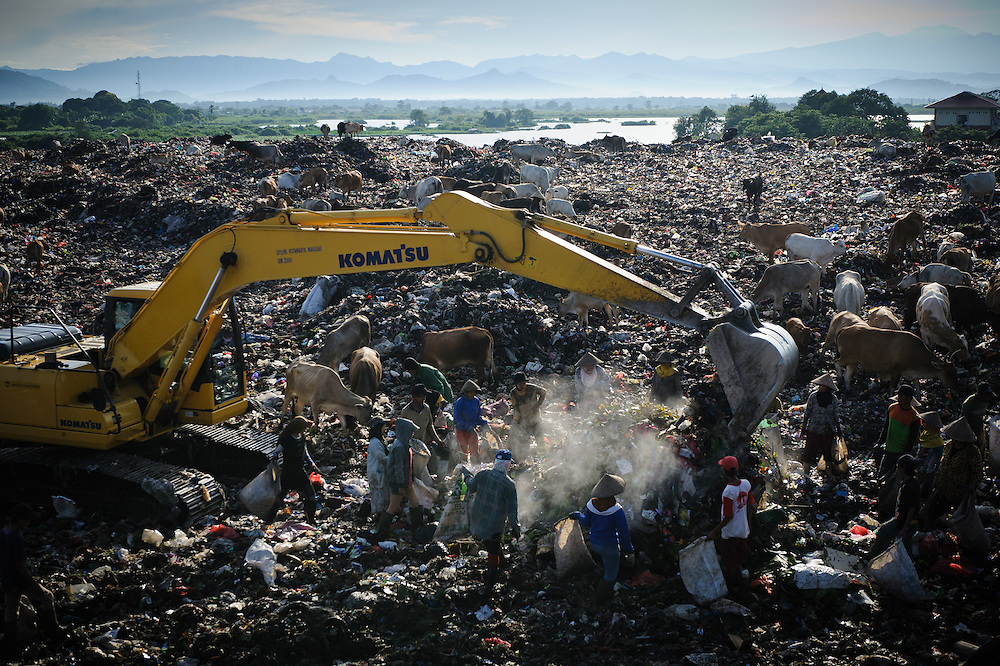 Pickers working alongside bulldozers and mechanical diggers at the 'Trash mountain', Makassar, Sulawesi, Indonesia.