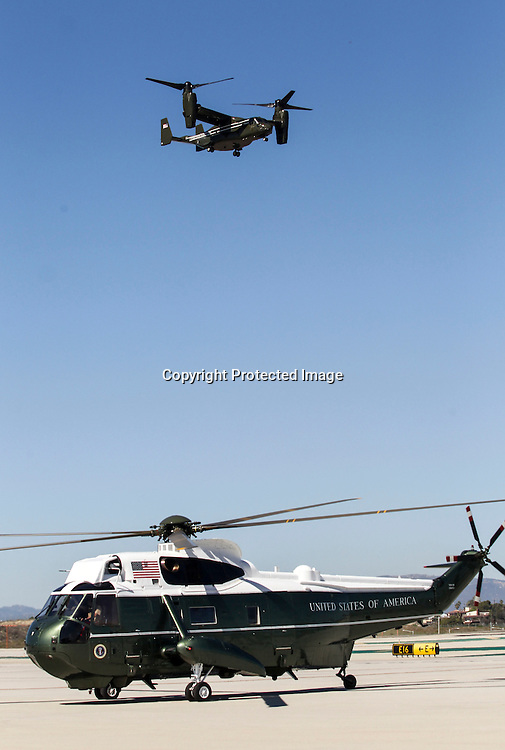 """An """"Osprey"""" aircraft flies over the Marine One before President Barack Obama's arrival at Los Angeles International Airport in Los Angeles on Saturday, Oct. 10, 2015. (AP Photo/Ringo H.W. Chiu)"""