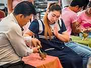 "14 FEBRUARY 2017 - BANGKOK, THAILAND: A couple prays while their wedding is blessed in the Bang Rak district in Bangkok. Bang Rak is a popular neighborhood for weddings in Bangkok because it translates as ""Village of Love."" (Bang translates as village, Rak translates as love.) Hundreds of couples get married in the district on Valentine's Day, which, despite its Catholic origins, is widely celebrated in Thailand.      PHOTO BY JACK KURTZ"