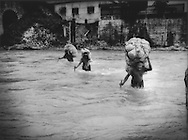 Guatemalan porters carry goods across the torrent of Rio Suchiate which forms the porous border between Guatemala and Mexico, Talisman, Mexico.