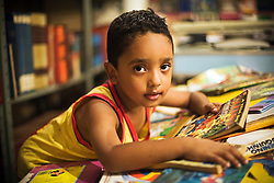 The boy was looking for new stories at the Prestes Maia Collective Library. The library started with a couple from Prestes Maia occupation, who were recycling the garbage from the streets in downtown. Mostly of the books were found in the garbage.