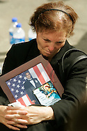 A family member of a victim in the World Trade Center attack holds a picture of her loved one Arturo Angelo Sereno at the site of the disaster on the fourth anniversary of the attack in New York September 11, 2005.