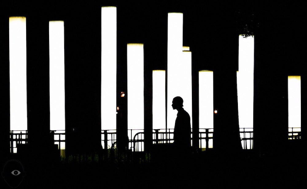 A lone individual walks past the illuminated columns in Battery Park within Lower Manhattan.